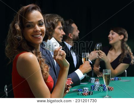 young brunette woman playing poker on black background