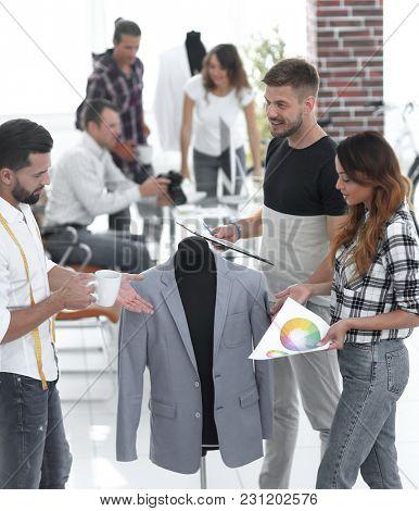 group of designers discuss men's suit