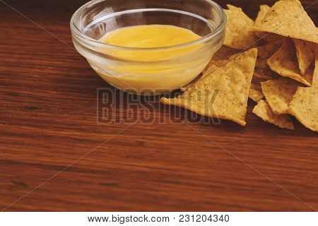Close Up View Of Nachos With Cheese Dip. Unhealthy Food Concept