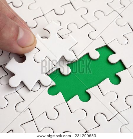 The Human Hand Fills The Last Missing Elements Of The Surface From The Jigsaw Puzzle. The Concept Of