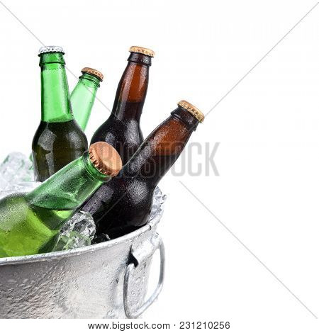 Closeup of green and brown beer bottles in a metal ice bucket, isolated on white.