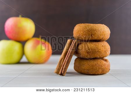 Apple Spice Donuts With Cinnamon Sticks And Apples In Pile