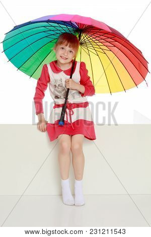 A Nice Little Girl Hid Under An Umbrella. The Concept Of A Happy Childhood, Outdoor Recreation, Prot