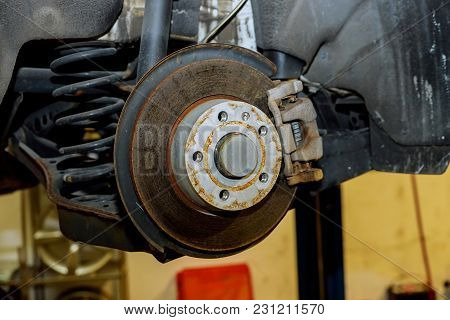 Rear Brake Disk With Caliper Partially Removed About To Be Replaced Brakes And Suspension