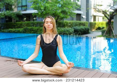 Sunset Portrait Of Fitness Woman Sit In Lotus Position Doing Yoga By Swimming Pool On Sunny Day. Con