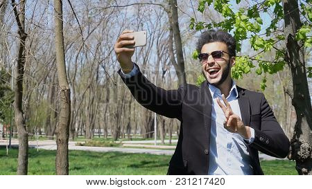 Man Showing Thumbs Up. Guy Opens Mouth And Smiles. Muslim Has White Teeth, Dark Hair And Beard, Wear