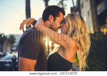 romantic couple kissing on sidewalk in los angeles