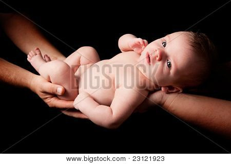 Naked Baby Boy Held Over Black Background
