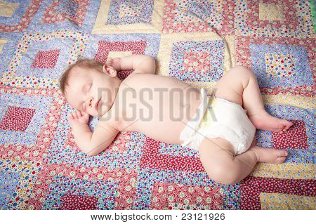 Sleeping Baby Boy In Diaper On Colorful Quilt