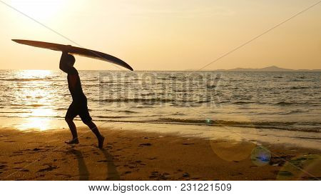 Silhouette Of Happy Surf Man Running With Long Surf Boards At Sunset On Tropical Beach. Surfer On Th