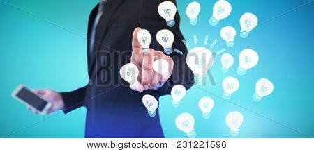 Mid section of businessman holding smartphone while using invisible interface against abstract blue background