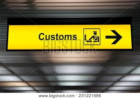 Airport Customs Declare Sign With Icon And Arrow Hanging From Airport Ceiling At International Termi