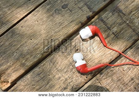 Red Earphone On Wooden Table Background For Entertainment Music Concept