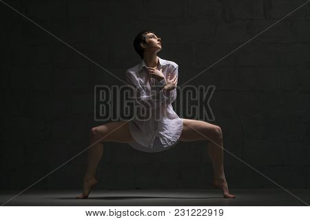 Sexy Girl With Shot Haircut Wearing White Shirt Dancing Gracefully In Dark Room Full-length Shot