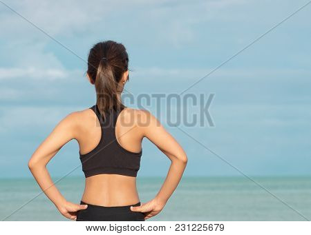 Back View Of Young Fitness Woman Running On The Beach In The Morning. People And Sport Concept