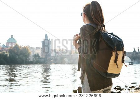 A Beautiful Young Tourist Girl With A Backpack Stands Next To The Vltava River In Prague And Admires
