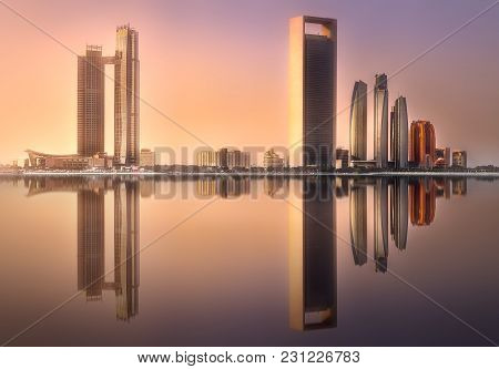View Of Abu Dhabi Skyline At Sunrise With Reflection On Water, United Arab Emirates