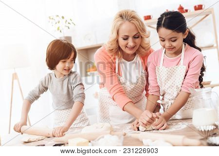 Happy Grandmother Together With Little Happy Grandchildren Knead Dough For Cookies In Kitchen. Grand