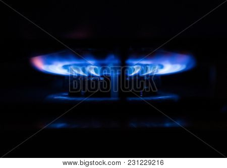 Close-up of blue fire burning from domestic kitchen stove in the dark