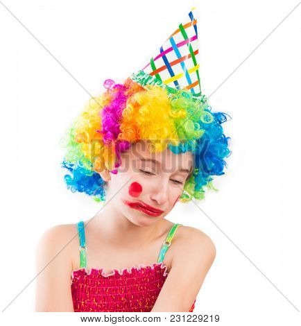 Upset little girl in clown wig and smeared make up isolated on white background