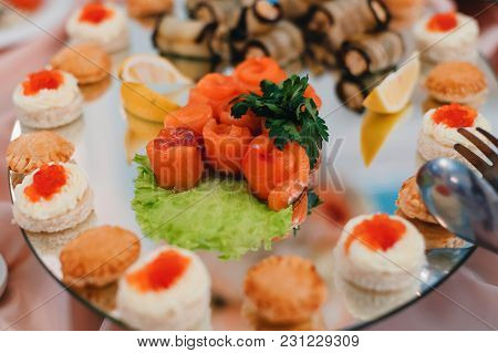 Salmon And A Variety Of Gourmet Dishes For A Snack On A Plate In The Restaurant