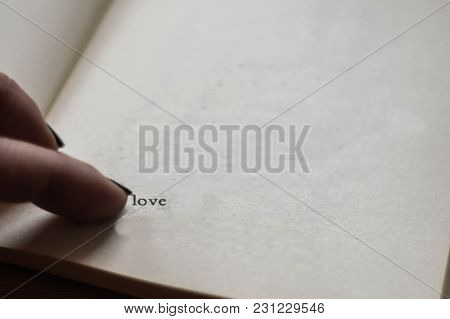 Woman Finger Whit Black Nail Pointed At Phrase Love In The Book/ Conceptual Image Of Love/ Saint Val