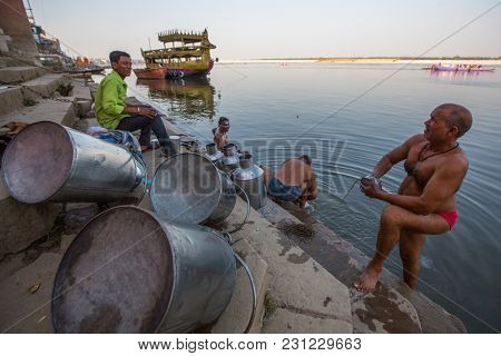 VARANASI, INDIA - MAR 13, 2018: Pilgrims on the banks of the Holy Ganga river. Varanasi is one of the most important pilgrimage sites in India and is one of the 7 sacred cities of Hinduism.