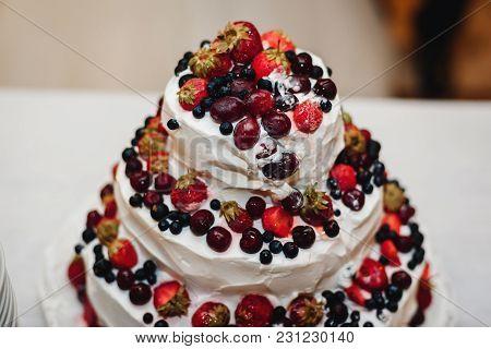 White Cream Wedding Cake With Fresh Sweet Strawberries, Cherries, Blueberries, Black Currants Close