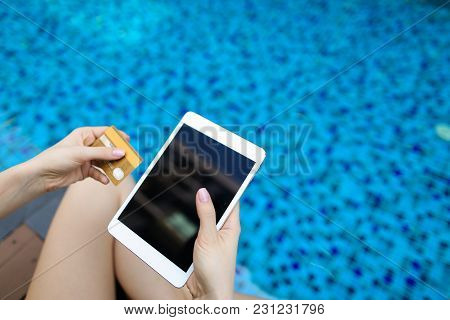 Bright Sunny Portrait Of Young Woman Hands Holding Gold Credit Debit Card And Laptop On Swimming Poo
