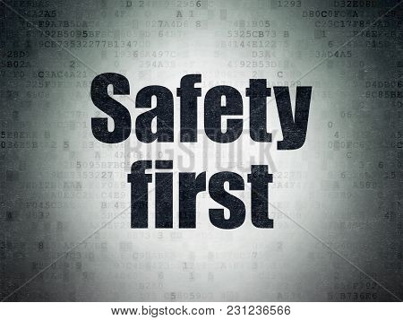 Safety Concept: Painted Black Word Safety First On Digital Data Paper Background