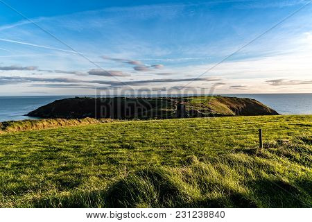 Scenic View Of Old Head Of Kinsale With Green Hills At Sunset.