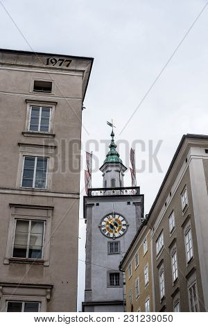 Low Angle View Of Clock Tower In Historic City Centre Of Salzburg A Cloudy Day