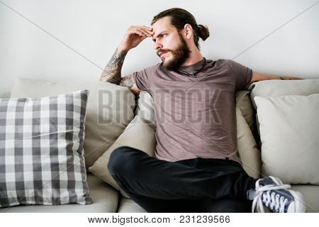 Man with tattoo sitting on a couch