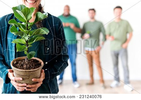 A woman holding a plant pot