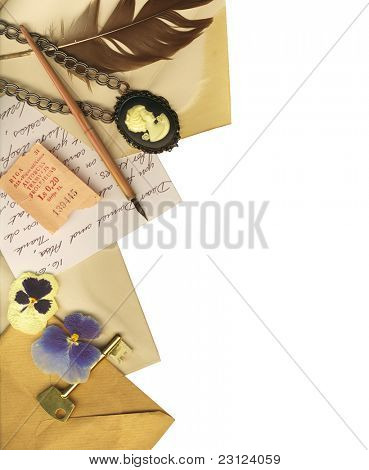 Clipping path. Vintage border with old letters, a key, a vintage ticket, flowers, a cameo and an old feather.