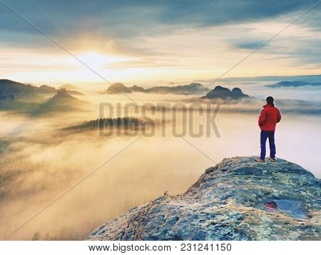 Rear View To  Traveler Stand Alone On Cliff With Mist Bellow Legs,  Sunshine In Cloudy Blue Sky