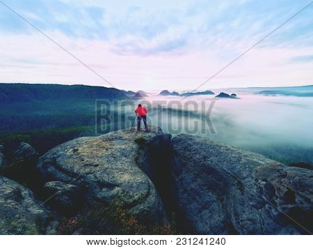 Professional Nature Photographer Above Clouds. Man Takes Photos With Camera On Tripod On Rocky Peak.