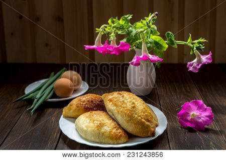 Pies And A Bouquet Of Petunias On A Wooden Table.