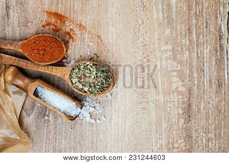 Flat lay of wooden spoons with spices,  coarse salt and cinnamon for cooking scatered on a table