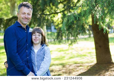 Handsome middle-aged man in park with his son. Attractive mid adult male model posing outddor with teen boy.
