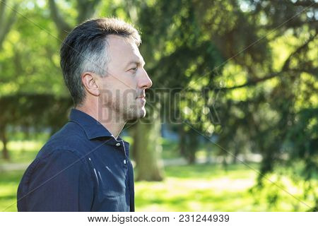 Handsome middle-aged man in park, portrait in profile.  Attractive mid adult male model posing outddor.
