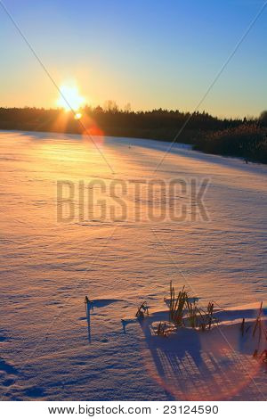 Winter sunset. Frozen lake