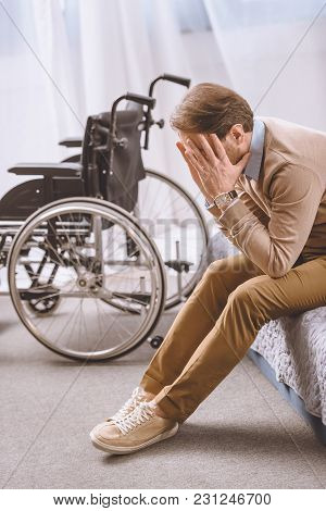 Stressed Man With Disability Sitting On Bed And Covering Face With Hands