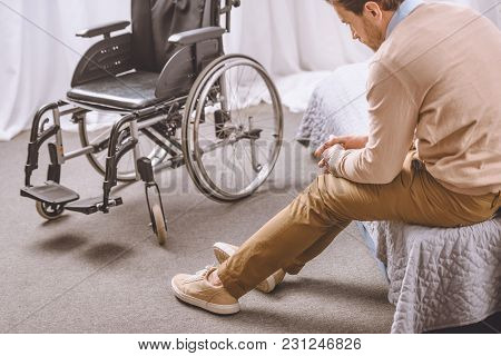 Sad Man With Disability Sitting On Bed, Wheelchair Standing Near