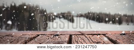 Snow falling against scenic view of landscape against sky