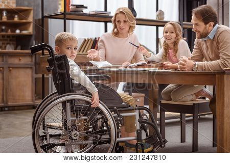 Sad Boy On Wheelchair Looking At Camera And His Relatives Laughing