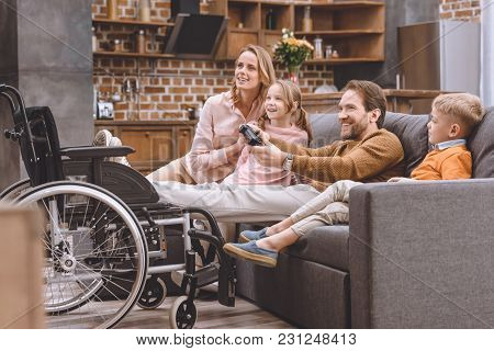 Happy Family With Disabled Father Playing With Joystick At Home