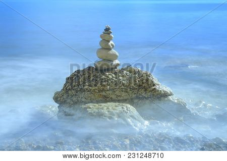 Pile Of Stones Surrounded By Blurred Sea Waves Near Village Of Beer In Devon On The Jurassic Coast N