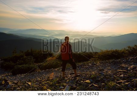 Hiker, Man Stands On The Edge Of The Cliff, Admiring The Panorama Of The Mountains In The Light Of T