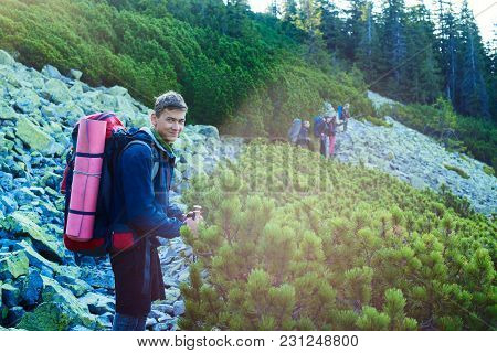Smiling Guy, Hiker Is Standing On A Rocky Path In The Company Of Friends, Admiring The Sunrise In Th